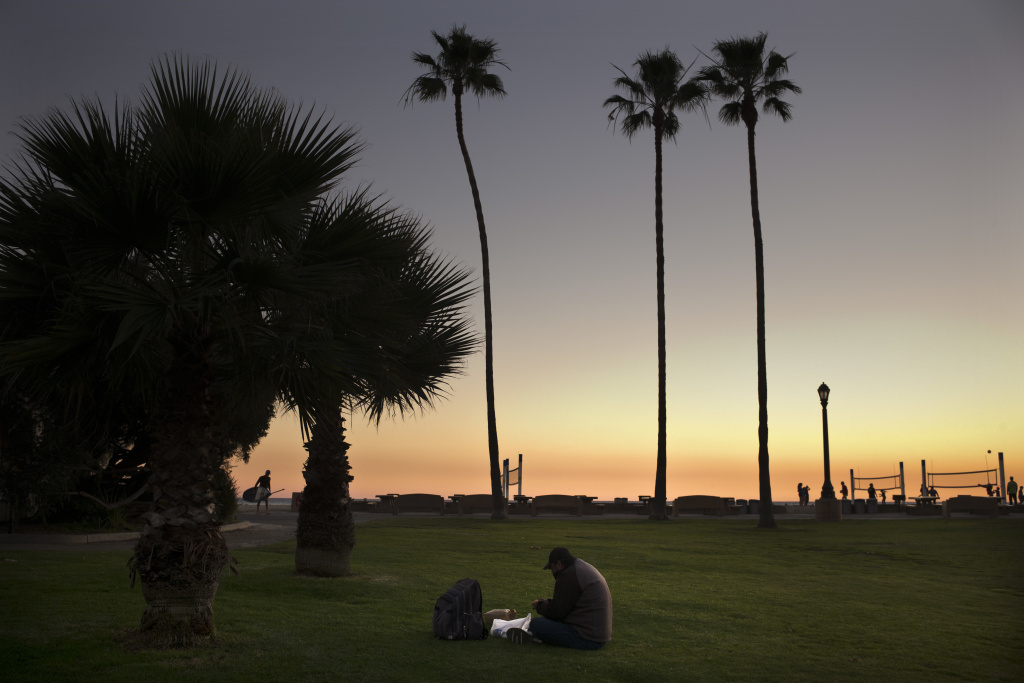 Sitting on the lawn at Doheny State Beach, Gholamreza Hagihgih, a 59-year-old Iranian immigrant who has been homeless for 20 years, eats his meal provided by a nonprofit organization Thursday, Dec. 21, 2017, in Dana Point, Calif. Goodhearted neighbors heartbroken over the rising number of homeless in their communities are dishing out hot meals, providing mobile showers and handing out sandwiches to those in need, hoping they can make a difference.