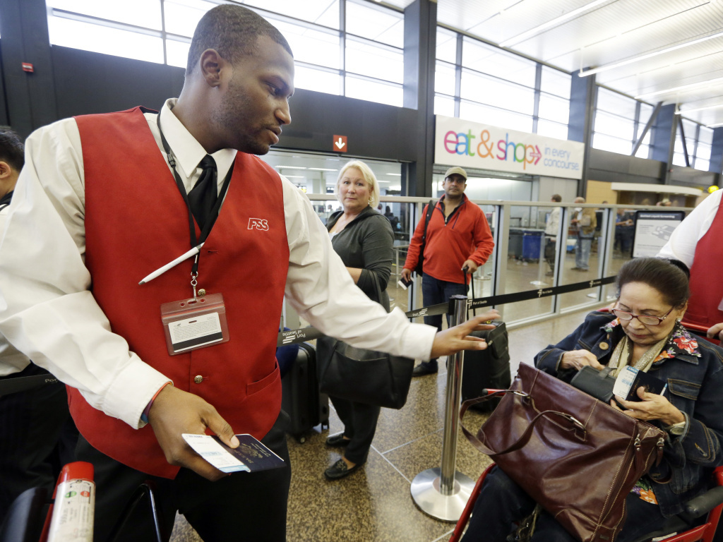Wheelchair attendant Erick Conley (left) assists an elderly passenger at Seattle-Tacoma International Airport in SeaTac, Wash. The small city recently raised the minimum wage to $15 for many airport jobs.