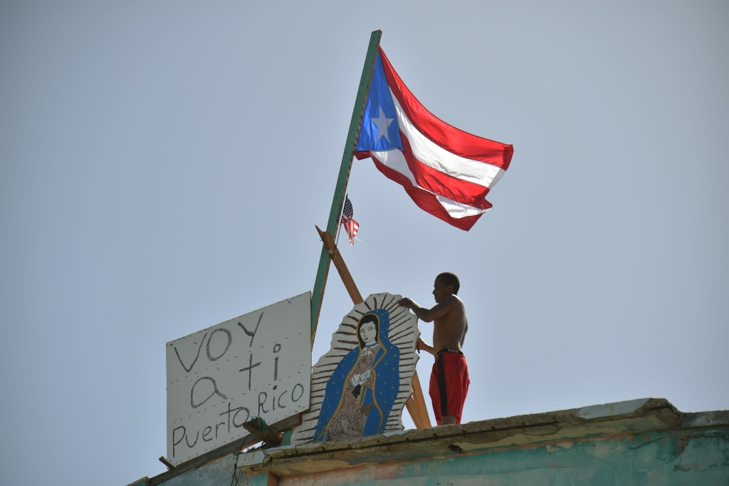 Javier stands on the roof of a home  in Yabucoa, next to a flag of Puerto Rico and a sign that reads