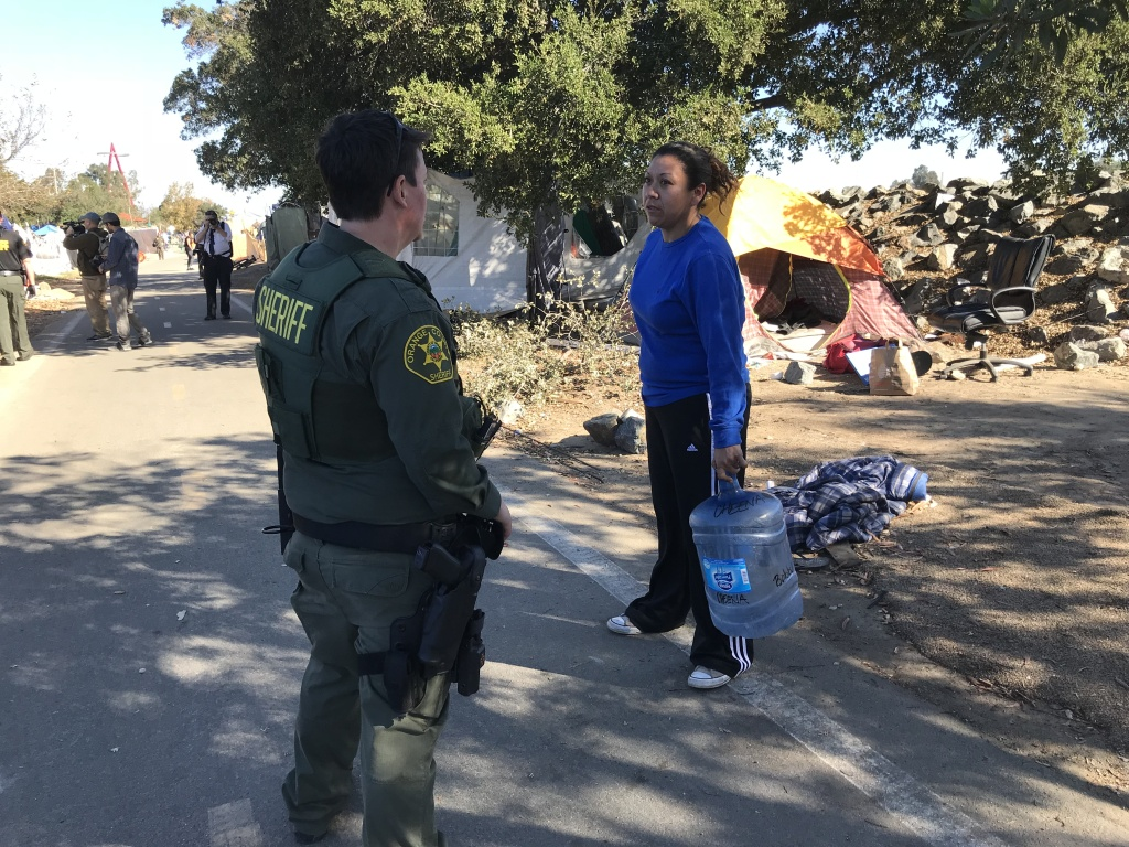 Orange County sheriff's deputy Molly Mussig talks to a resident about moving off of the Santa Ana riverbed on Monday, January 22, 2018.
