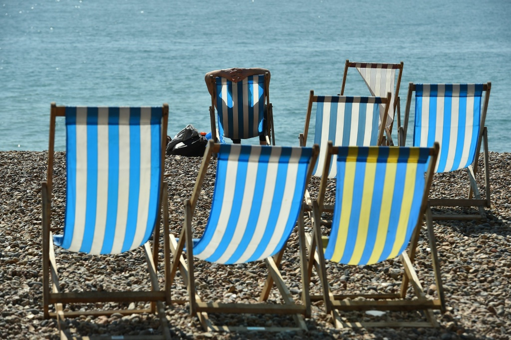 A man sits in a deckchair as people enjoy the weather conditions as they sit on Brighton beach on the south coast of England.
