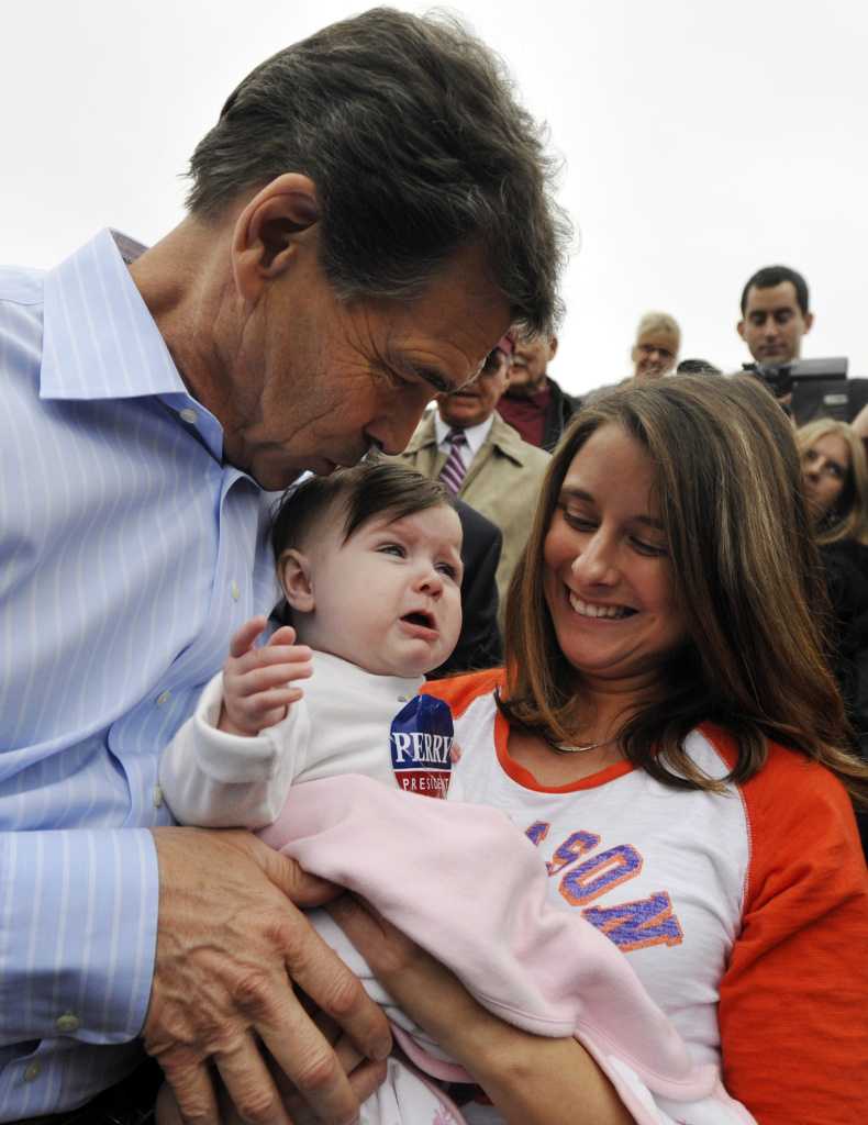 SPARTANBURG, SC- JANUARY 8: Republican presidential candidate, Texas Gov. Rick Perry (L) kisses 7-month-old Elaina Stephens, as her aunt Candi Tennyson (R) looks on during a campaign stop at the Beacon Drive-In January 8, 2012 in Spartanburg, South Carolina. After suffering a fifth place finish in the Iowa caucuses, Gov. Perry has returned to the campaign trail in South Carolina with events for the next several days in hopes of keeping his candidacy alive.