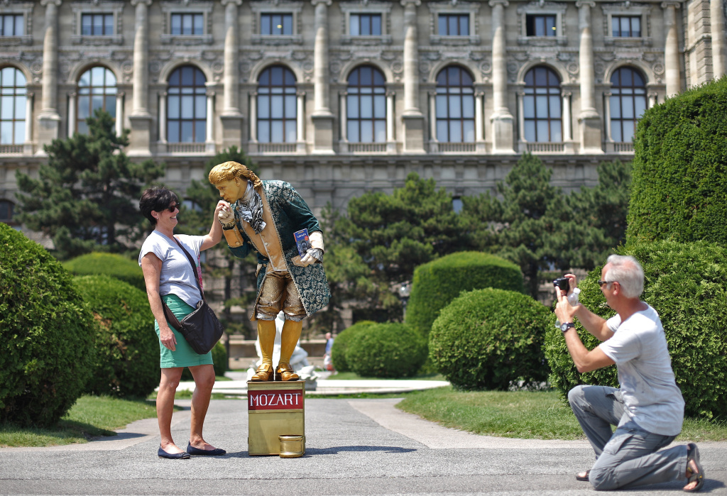 Tourists take a picture next to a street artist dressed up as Mozart on a hot and sunny day in Vienna, on June 20, 2012.