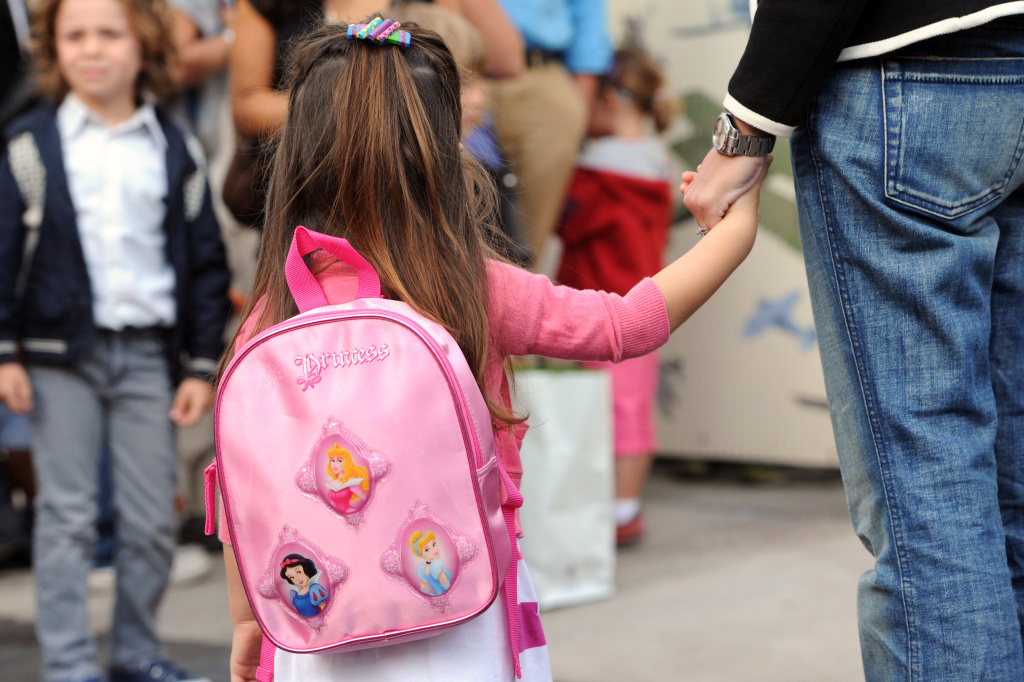 A pupil holds the hand of her mother in the courtyard of a school prior to entering in her classroom for an early start of the new school year.
