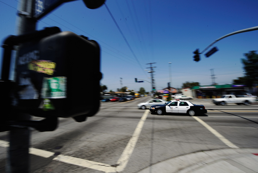 A Los Angeles Police Department car with lights and sirens going rushes through the intersection at Florence and Normandy Avenues in South Los Angeles on April 27, 2012 in Los Angeles, California.