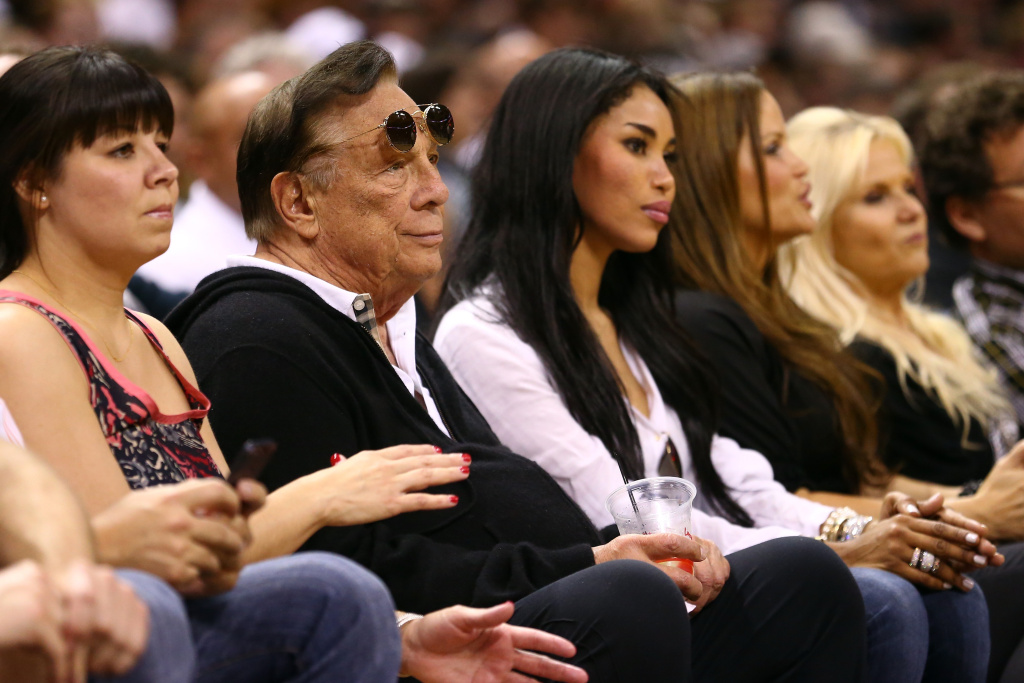 Alleged comments by LA Clippers owner Donald Sterling are losing the team sponsorships. Here, he watches a game with girlfriend V. Stiviano last year.