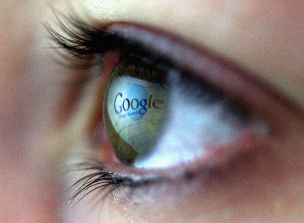 The Google logo is reflected in the eye of a girl surfing the internet.