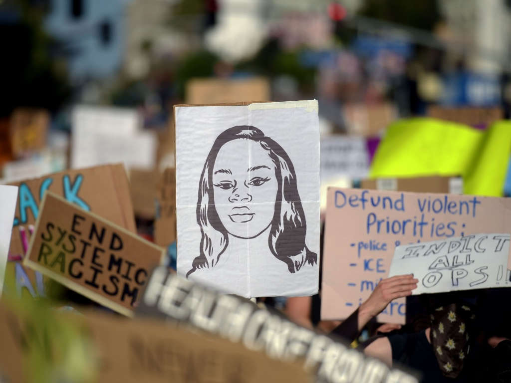 Protesters march holding placards and a portrait of Breonna Taylor during a demonstration against racism and police brutality in Hollywood, California earlier this month.The mayor of Louisville has announced that an officer involved in her death will be fired.