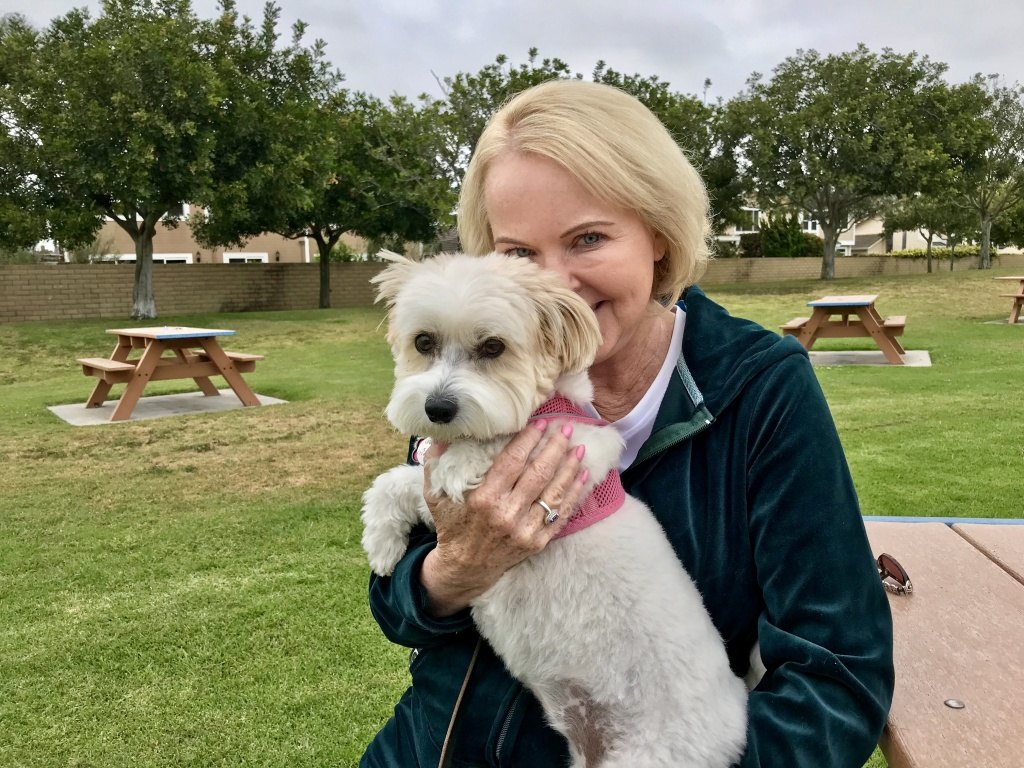 Jan Curtis and her dog, Belle, at a park near her Huntington Beach home on April 27, 2018. Curtis hopes she's nearing the end of a decades-long struggle with chronic pain and the opioid dependence that came with it.