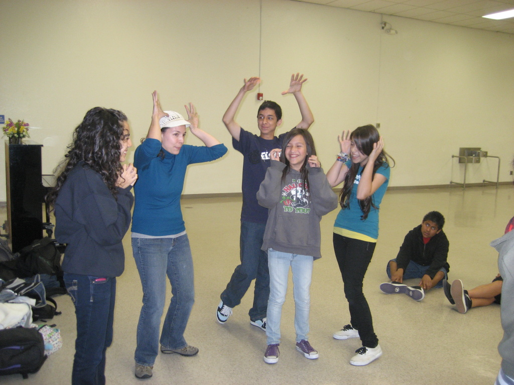 A Cal Arts grad student helps kids learn to mime during a theater arts workshop for English learners.