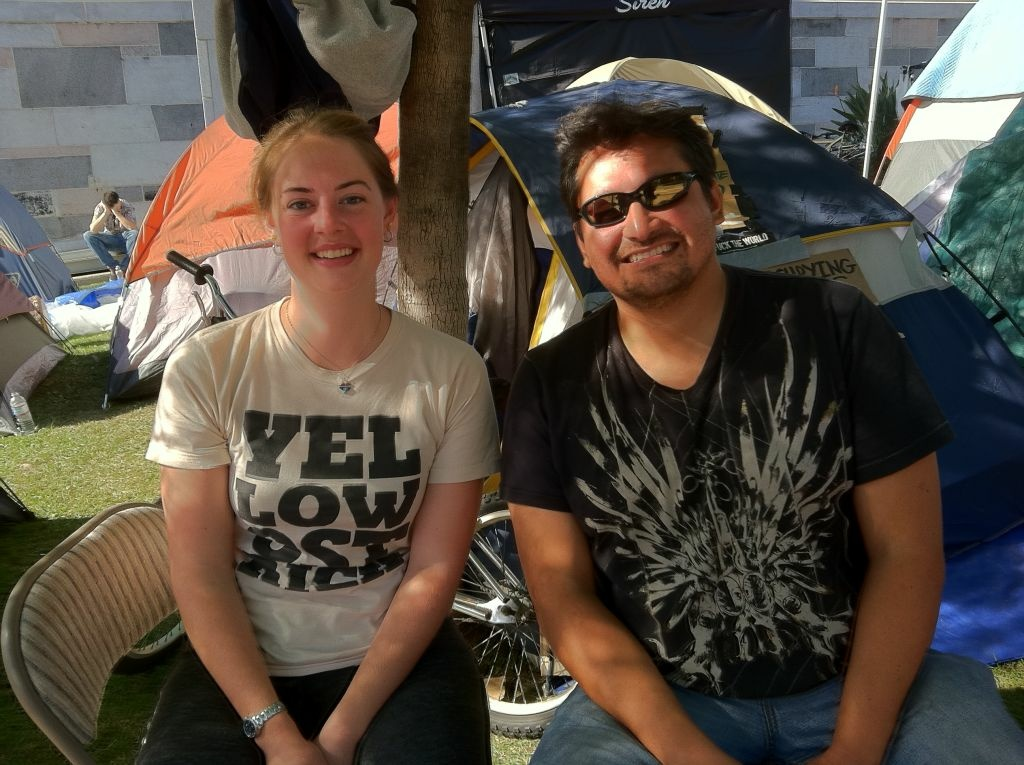Elise Whittiker, 21, and Mario Brito, 38, sit outside Elise's tent, on the north lawn of LA City Hall.