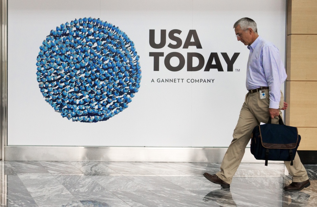 In this file photo, a man walks through the lobby of the Gannett-USA Today headquarters building August 20, 2013 on a 30-acre site in McLean, Virginia. Los Angeles Times parent company Tribune Publishing confirmed Monday that it received an unsolicited offer from Gannett Co. and said it