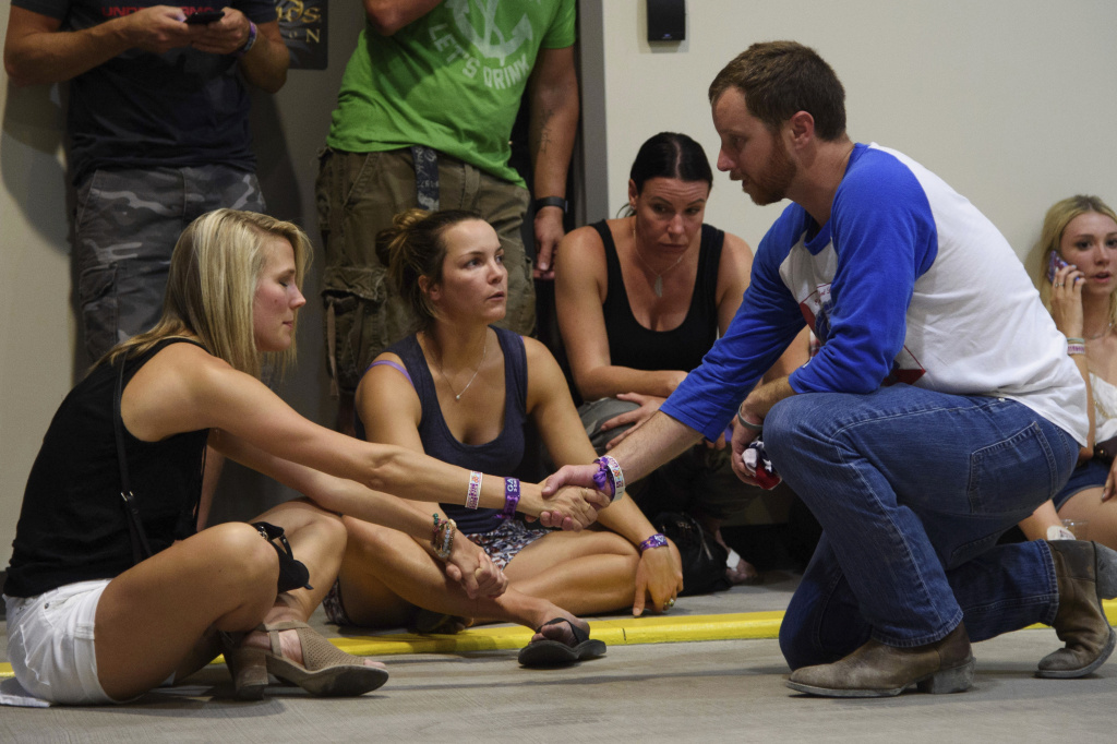 People hold hands in prayer while hiding inside the Sands Corporation plane hangar after a mass shooting in which dozens were killed at the Route 91 Harvest Festival on Sunday, Oct. 1, 2017, in Las Vegas.