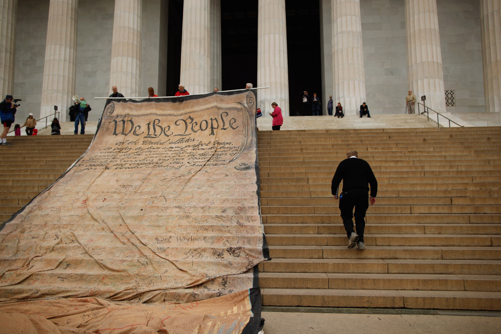 Laird Monahan walks up the steps of the Lincoln Memorial past a giant banner printed with the Preamble to the United States Constitution during a demonstration against the Supreme Court's Citizens United ruling on the National Mall October 20, 2010 in Washington, DC.