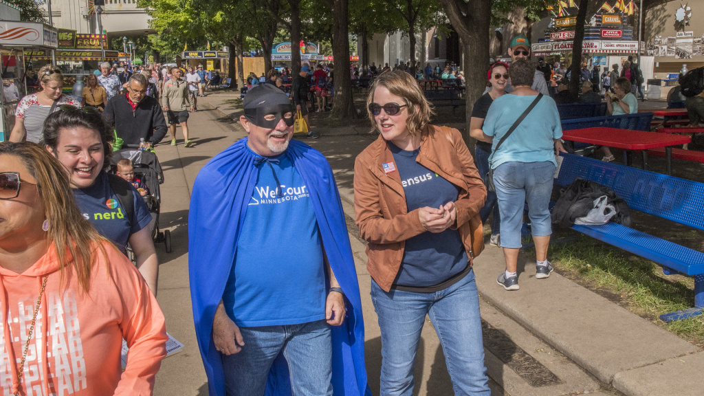Minnesota's state demographer, Susan Brower (center), walks with Dean Goldberg, donning a blue cape and black mask as