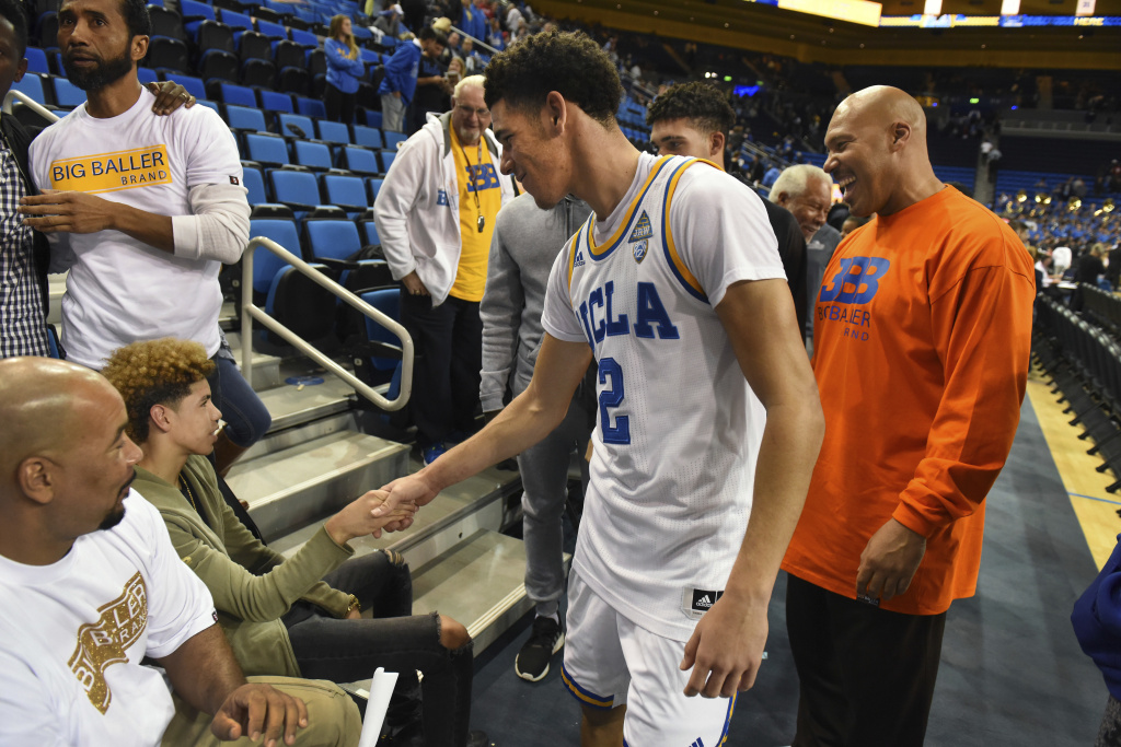 FILE - In this Nov. 20, 2016, file photo, UCLA's Lonzo Ball (2) greets his brother LaMelo Ball, left, after scoring 20 points in UCLA's 114-77 win over Long Beach State in an NCAA college basketball game in Los Angeles. Behind Lonzo Ball are his brother LiAngelo Ball and father, LaVar Ball, right.