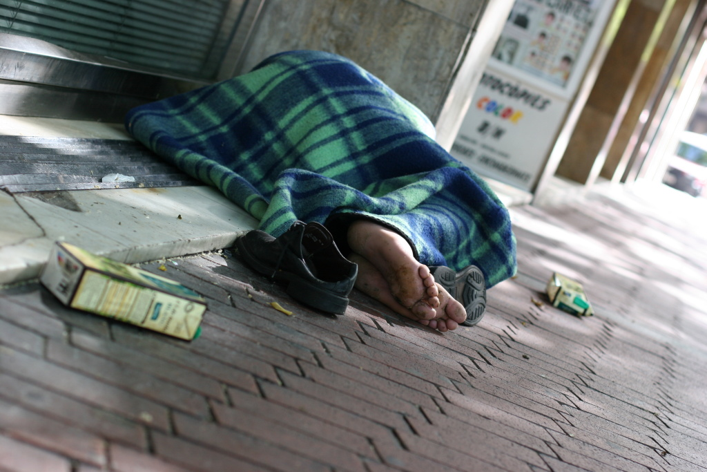 File: A person sleeps on a sidewalk in Los Angeles.