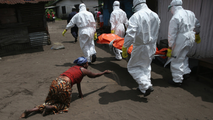 Umu Fambulle stands over her husband, Ibrahim, who'd fallen and knocked himself unconscious in an Ebola ward in Monrovia, Liberia.