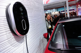 An attendee looks GE's new Residential WattStation plugged into a Chevrolet Volt electric car at the 2011 International Consumer Electronics Show January 8, 2011 in Las Vegas.