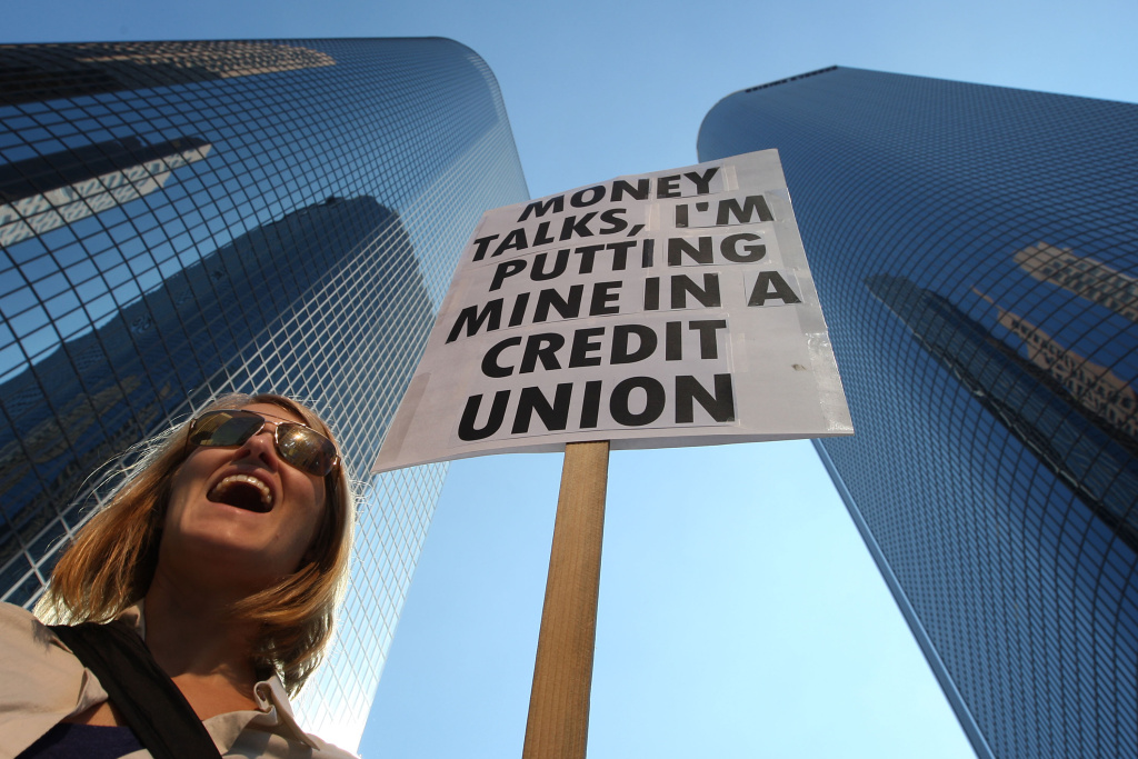 LOS ANGELES, CA - NOVEMBER 5:  Molly Hawkey, who moved her money from a bank to a credit union this week, carries her sign in the downtown financial district during during the the Move Your Money March on what is being called Bank Transfer Day on November 5, 2011 in Los Angeles, California. Occupy movement members are calling for people to move their money from banks to credit unions today in support of the 99% movement.   (Photo by David McNew/Getty Images)
