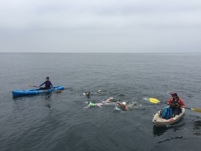Kerry Yonushonis swims between two kayakers during her journey across the Catalina Channel.