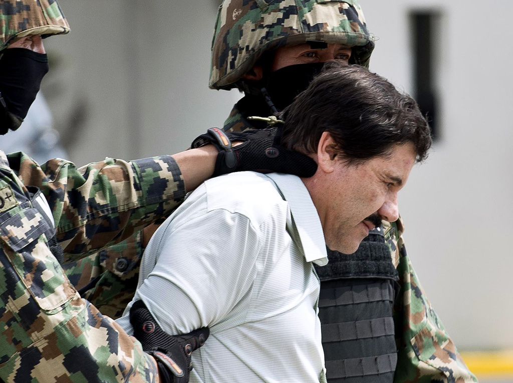Mexican drug trafficker Joaquin Guzman Loera aka 'el Chapo Guzman' is escorted by marines as he is presented to the press on Feb. 22, 2014 in Mexico City. The Sinaloa cartel leader - the most wanted by U.S. and Mexican anti-drug agencies - was arrested early Saturday morning by Mexican marines at a resort in Mazatlan, northern Mexico.