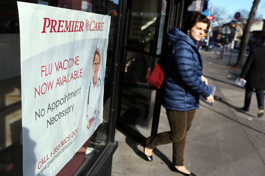 A woman walks out of the Premier Care walk-in health clinic which administers flu shots on January 10, 2013 in New York City. The flu season has hit parts of the country particularly hard this year and is now widespread in California.