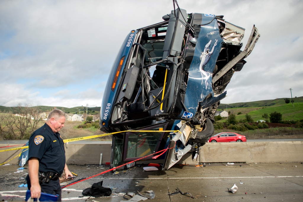 File: A California Highway Patrol officer moves belongings from a Greyhound bus crash Tuesday, Jan. 19, 2016, in San Jose.