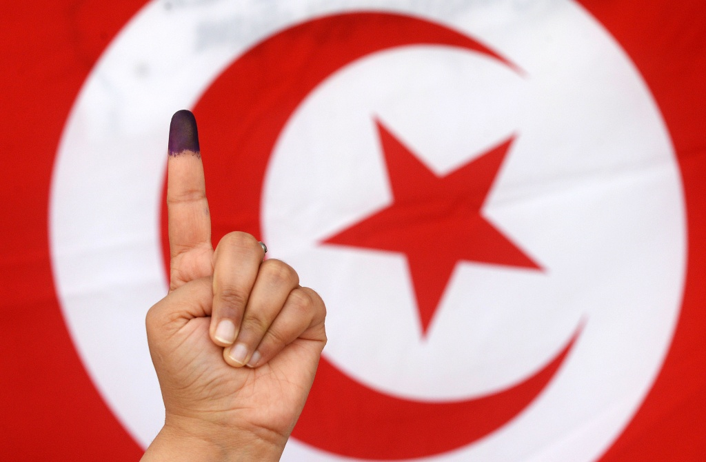 A Tunisian woman raises her ink-stained finger in front of a national flag after casting her vote in the country's first post-revolution presidential election on November 23, 2014, at a polling station in the capital Tunis.