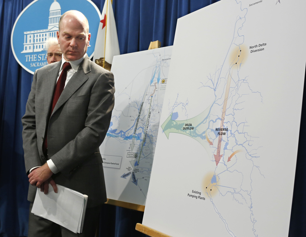 Chuck Bonham, director of the California Department of Fish and Wildlife Services, glances at a diagram showing the water flow into and out of the Sacramento-San Joaquin Delta, during a news conference at the Capitol in Sacramento, Calif., Thursday, March 14, 2013.  California water officials unveiled the revisions of the first four draft chapters of a $23 billion plan to restore and protect the Sacramento-San Joaquin Delta ecosystem and guarantee a stable water supply for millions of Californians. The Bay Delta Conservation Plan, known as the BDCP for short, is a federal and state initiative financed by California's water contractors, which includes recommendations for a twin tunnel project in the delta to carry water to vast farmlands and cities.