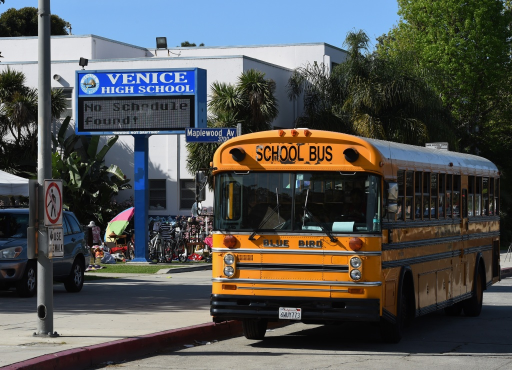 A school bus is parked outside the Venice High School, where police are investigating allegations of the sexual assault of students at the school in Venice Beach, California on March 14, 2015.  Police today are continuing their search for four male suspects who were allegedly part of a group of 14 accused of sexually assaulting two underage girls at the school.