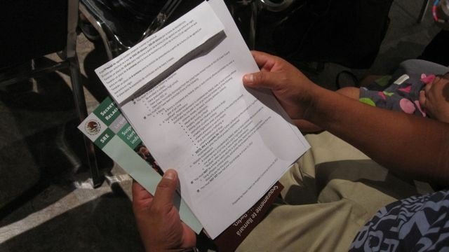 A man holds a list of guidelines during a deferred action applicants' workshop at the Mexican consulate in Los Angeles, August 14, 2012
