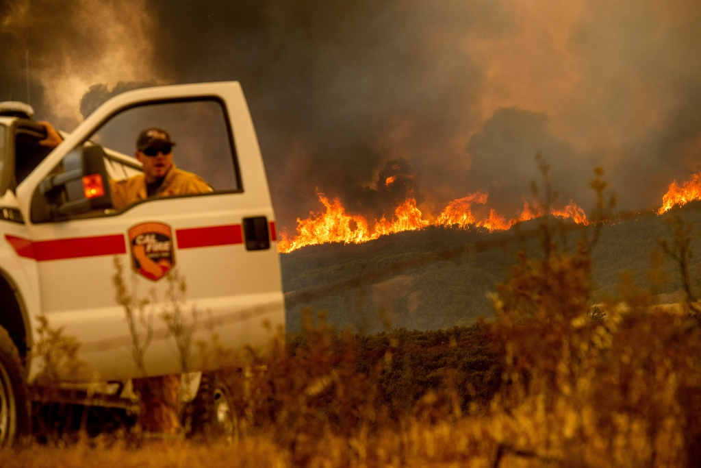 The Ranch Fire, part of the Mendocino Complex Fire, crests a ridge as Battalion Chief Matt Sully directs firefighting operations on High Valley Rd. near Clearlake Oaks, California, on Sunday, Aug. 5, 2018. (Photo by NOAH BERGER / AFP)        (Photo credit should read NOAH BERGER/AFP/Getty Images)