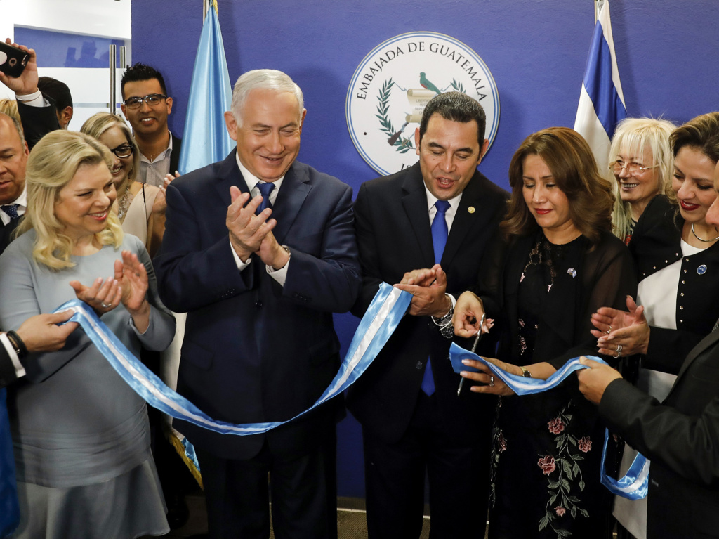 Israeli Prime Minister Benjamin Netanyahu and Guatemalan President Jimmy Morales, flanked by their wives, cut the ribbon during a ceremony Wednesday inaugurating the Guatemalan Embassy in Jerusalem.
