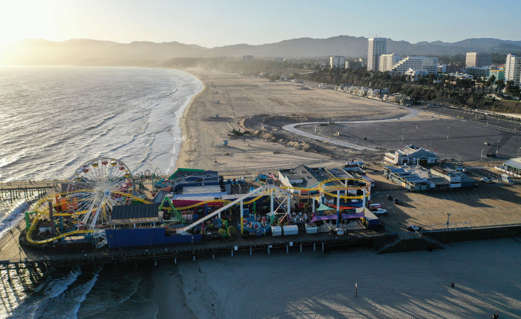 An aerial view of the shuttered Santa Monica Pier on Santa Monica Beach before sunset, on the day Los Angeles County reopened its beaches which had been closed due the coronavirus pandemic, on May 13, 2020 in Santa Monica, California.