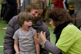 A child expresses his discomfort as he's given a shot.