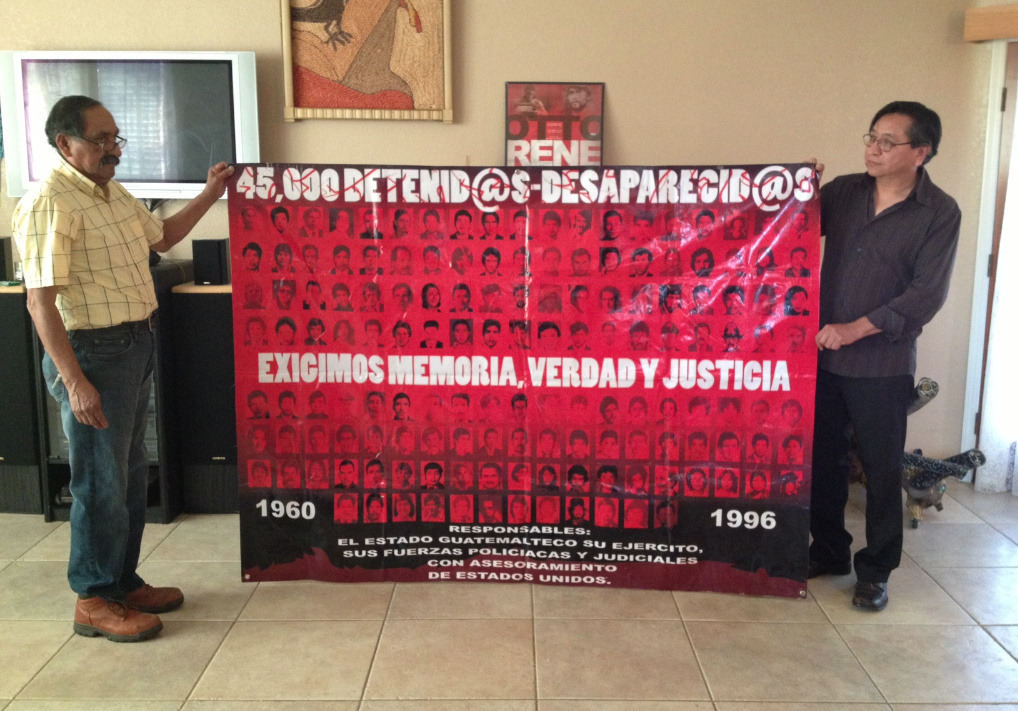 Mario Avila, left, and Eduardo Estrada hold up a banner memorializing Guatemala's wartime