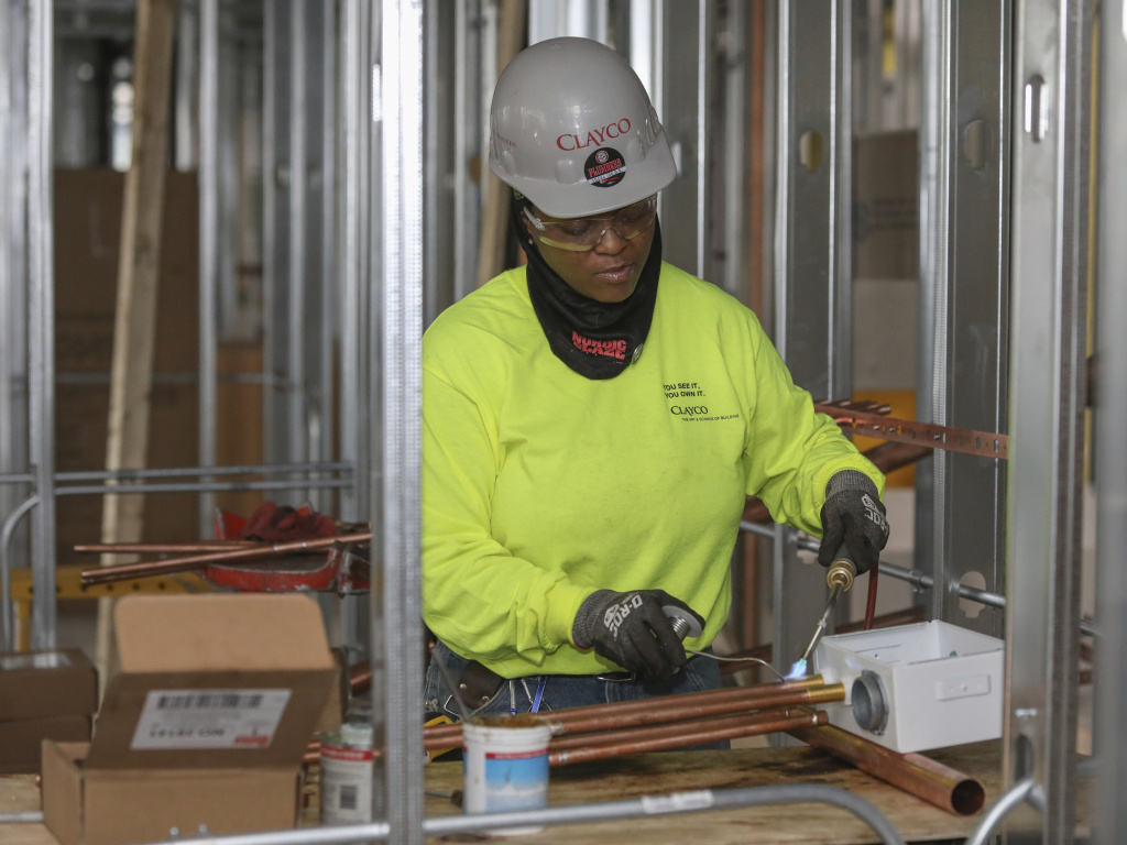 Plumber Zakiyyah Askia welds pipes at a high-rise residence under construction in Chicago on Jan. 24. Analysts see a rebound in March's employment numbers. Only 20,000 jobs were added in February.