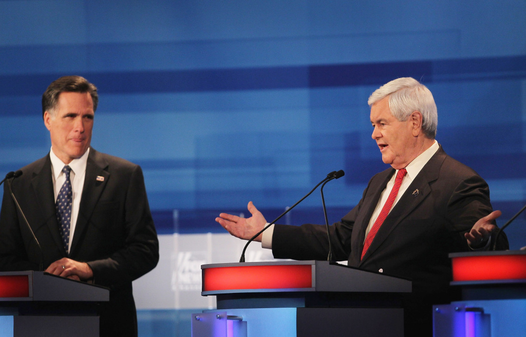 Republican presidential candidate former Massachusetts Gov. Mitt Romney (L), listens as former Speaker of the House Newt Gingrich answers a question during the Fox News Channel debate at the Sioux City Convention Center on December 15, 2011 in Sioux City, Iowa.