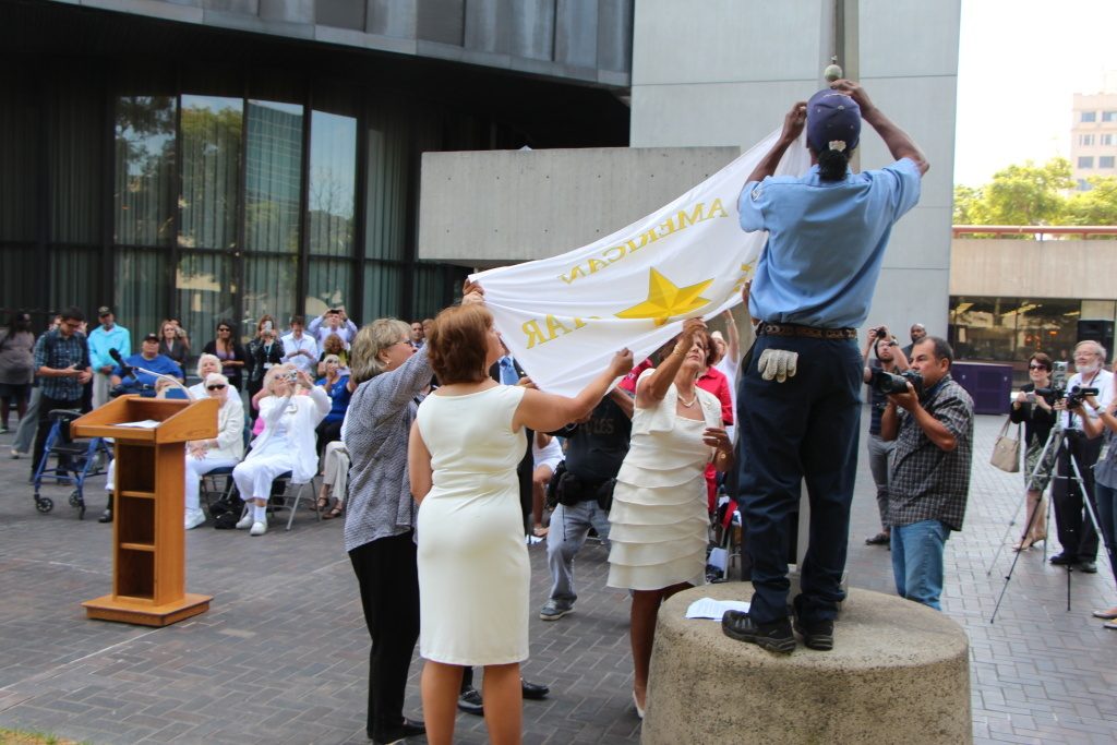 A flag honoring U.S. parents of military service members killed on duty during war is raised Aug. 15, 2013 at Long Beach City Hall Plaza. The women dressed in white are members of the American Gold Mothers, who have suffered the loss of a son or daughter in war.