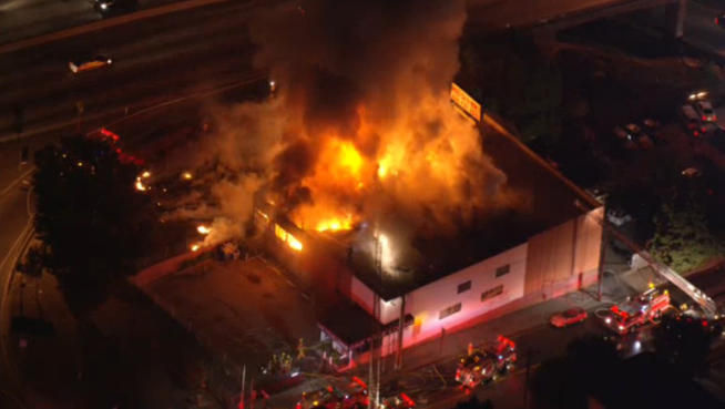 Firefighters work to extinguish flames that consumed a three-story building Tuesday night near the 101 Freeway in Hollywood.