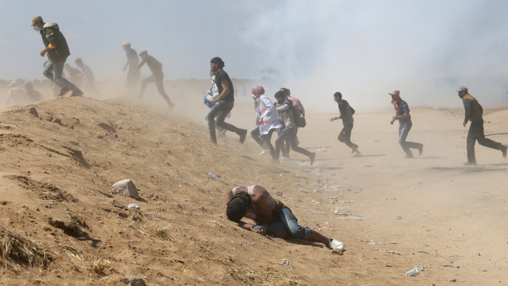 Palestinian demonstrators run or take cover from tear gas fired by Israeli forces at the Israel-Gaza border.
