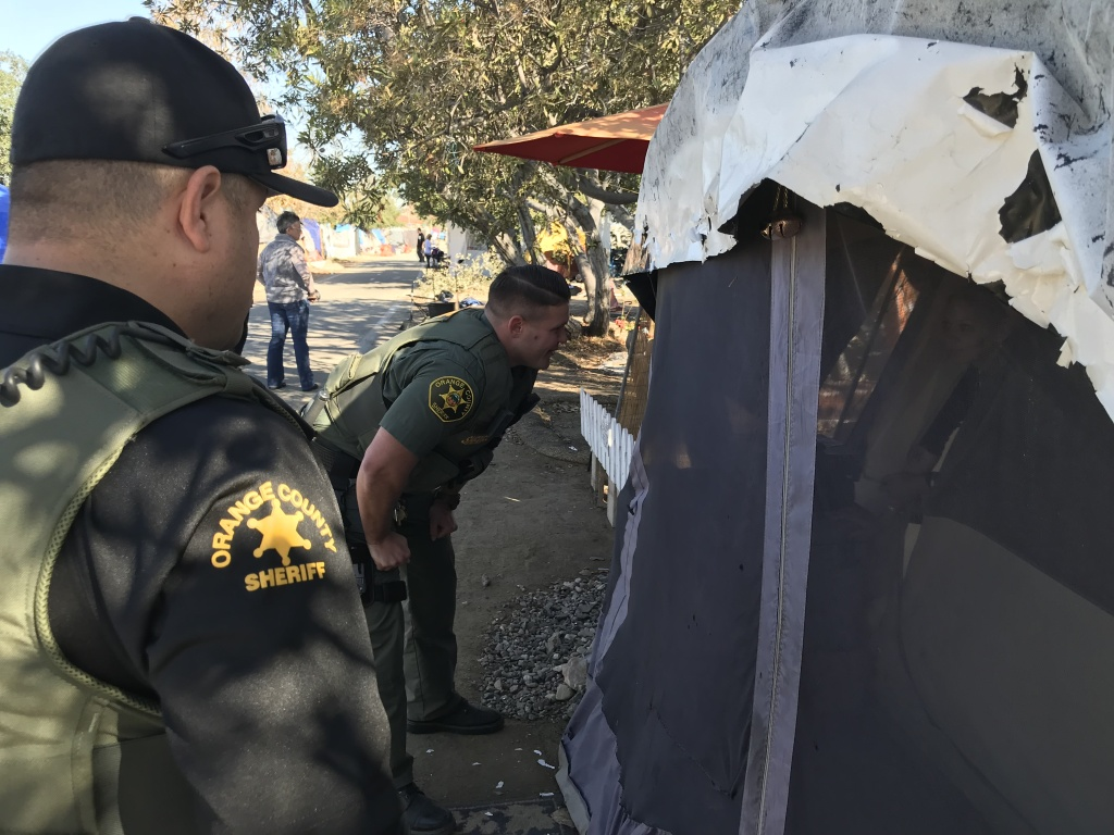 Orange County sheriff's deputies on Monday began going tent to tent along the Santa Ana River telling people the area will be closed and they need to move.
