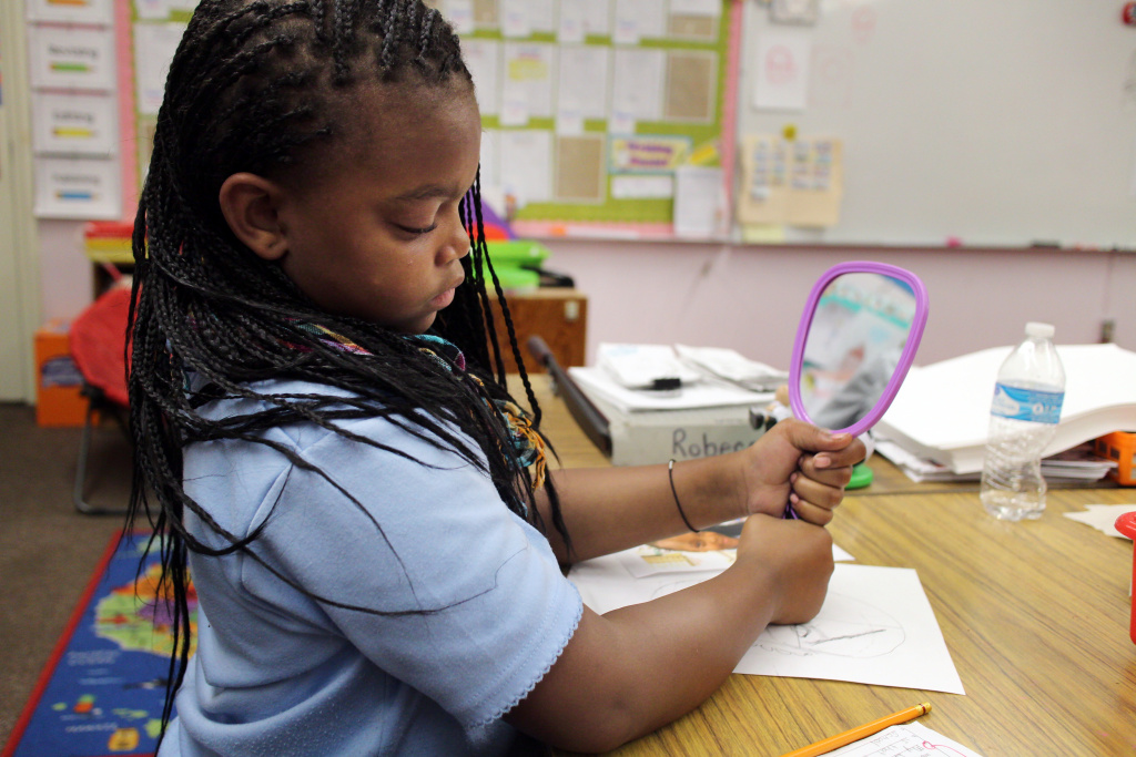 Fourth grader Samir Davis checks out her features in the mirror as she sketches. For most of the students, the nose is the hardest part.