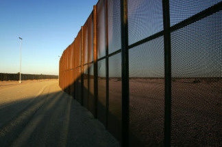 A metal fence constructed by National Guardsmen forms a double-fence border barrier in a dusty no-man's land of denuded desert that runs along the US-Mexico border on October 4, 2007 east of San Luis, Arizona.