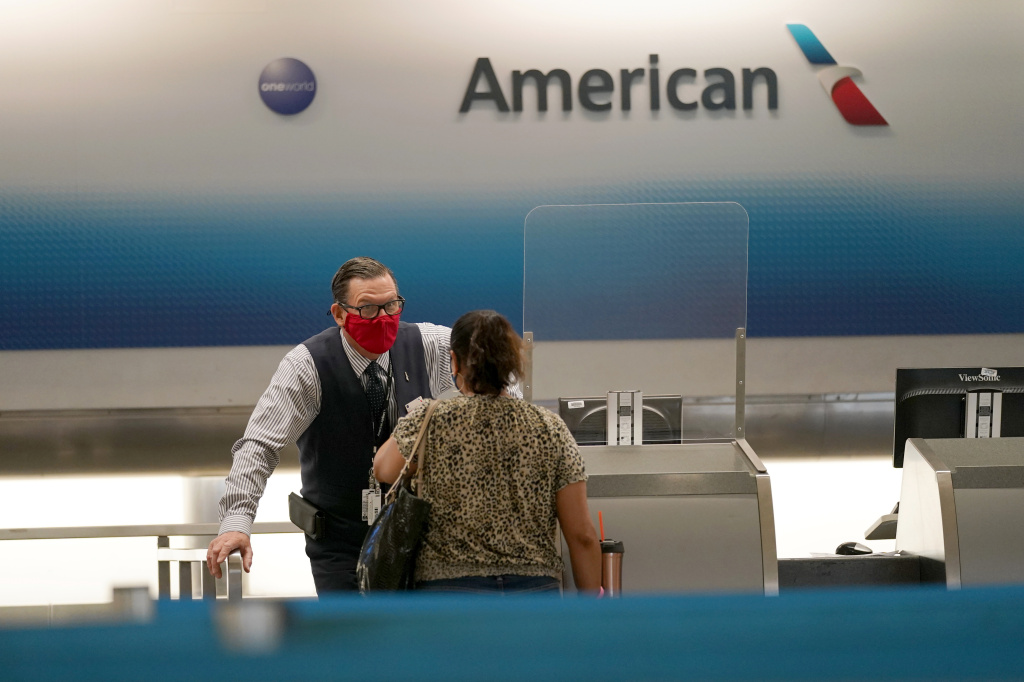 American Airlines ticket agent Henry Gemdron, left, works with a customer at Miami International Airport on Sept. 30. Travel industry groups warn of huge job losses if Congress and the White House fail to reach agreement on coronavirus relief soon.