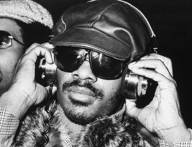Stevie Wonder listening to headphones