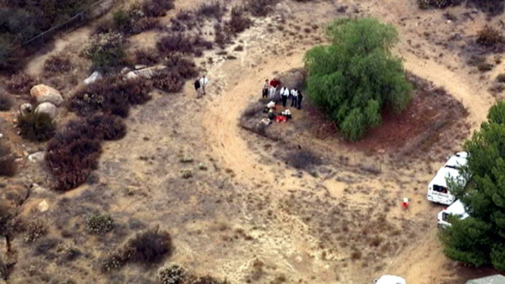 Investigators dig behind a Menifee property in the search for a missing 11-year-old autistic boy on Wednesday July 10, 2013.