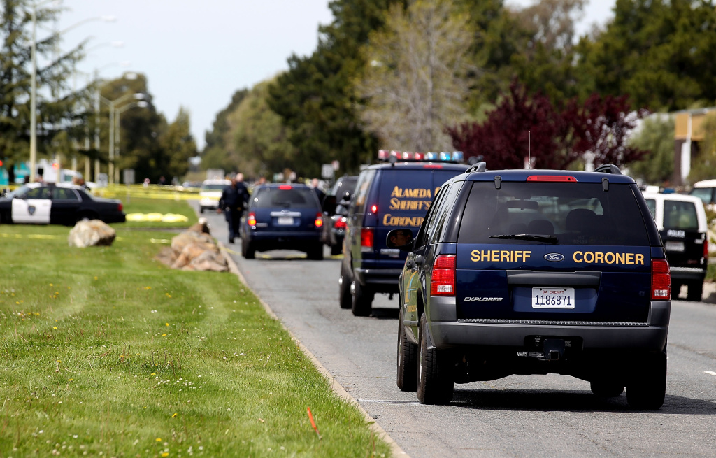 Sheriff coroner vans drive to the bodies of the shooting victims at Oikos University as police survey the scene on April 2, 2012 in Oakland, California.