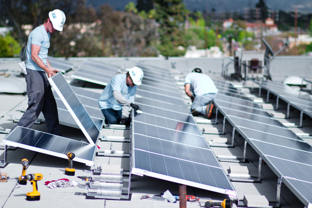 Workers install solar panels on the roof of the North Hollywood apartment complex participating in the program that lets businesses sell solar power from large-scale rooftop arrays to the L.A. Department of Water and Power.